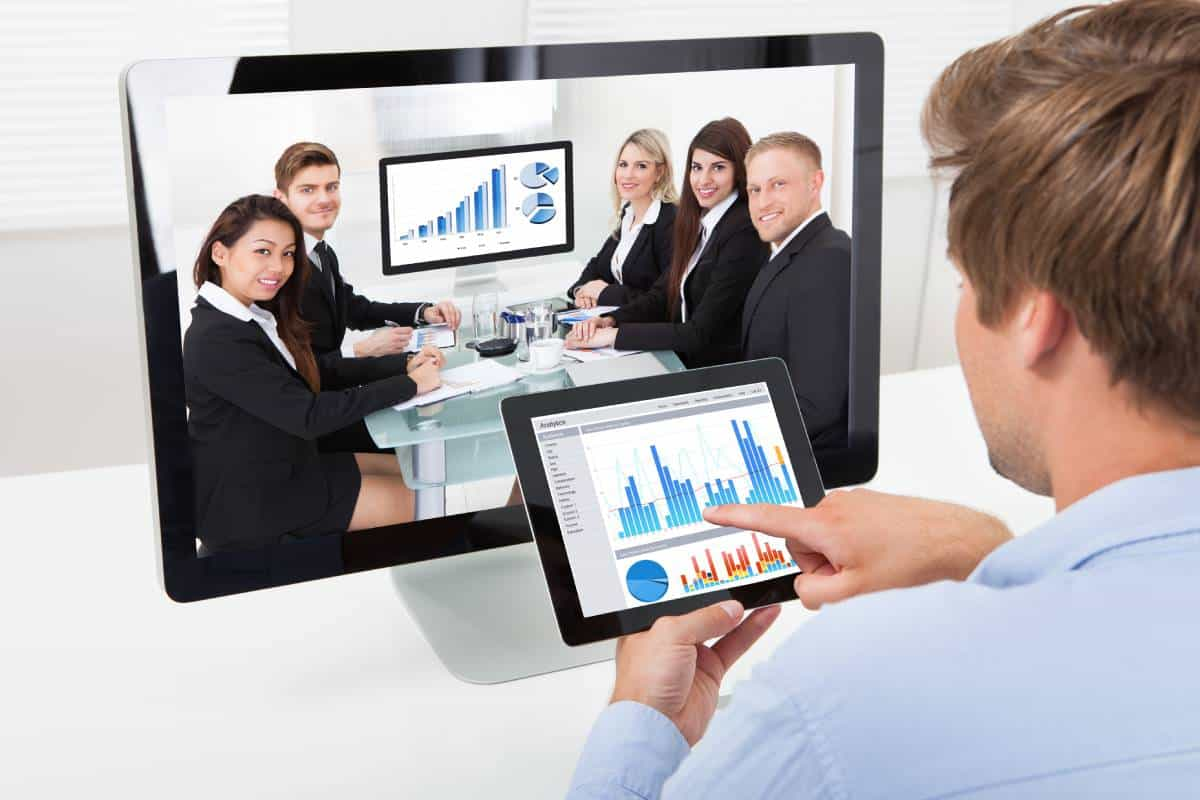 Man using a tablet showing graphs, video conferencing with colleagues