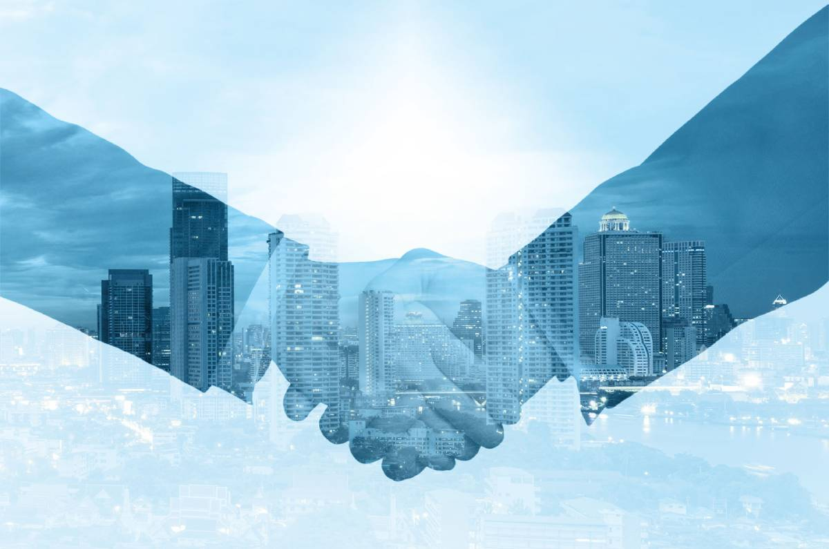 Two businessmen shaking hands on a blue background with a city skyline