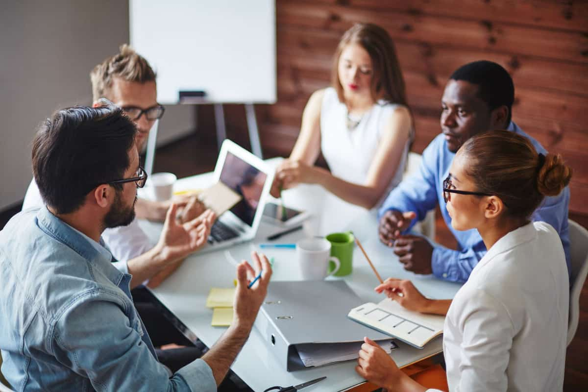 5 Young Business People Around a Small Meeting Table