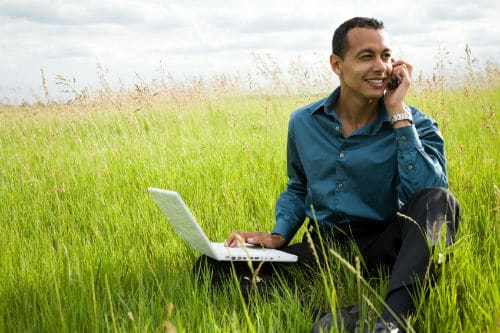 Man with laptop in field